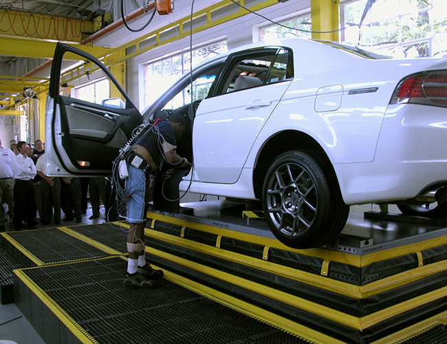 Man working on a white car that is lifted up by SPC Industrial products.